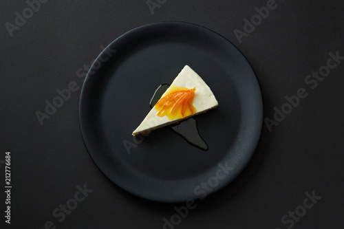 Poster Plat cuisine Dessert of cheesecake with jam on a black plate isolated on a black background