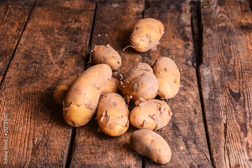 Obraz na plátně Kartoffel Gruppe auf Holztisch rustikal