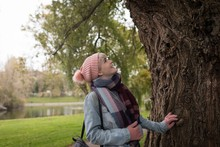 Woman In Winter Clothing Looking At Tree