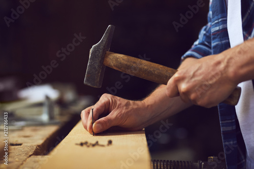 Fototapeta Carpenter hammering a nail into wooden plank in a carpentry shop