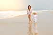 A young beautiful girl in a white shirt runs along a sandy beach in the sea with her son in white clothes and hat