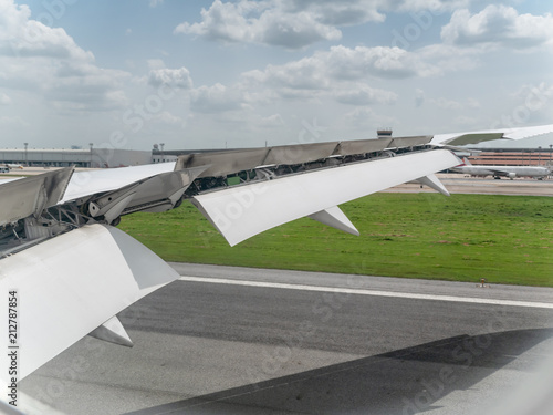Landing aircraft at the airport, Braking of the aircraft on the runway, wing of the plane is in working order Wallpaper Mural