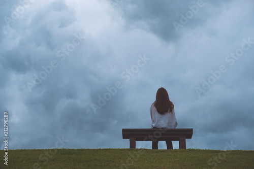 Fotografia A woman sitting alone on a wooden bench in the park with cloudy and gloomy sky b