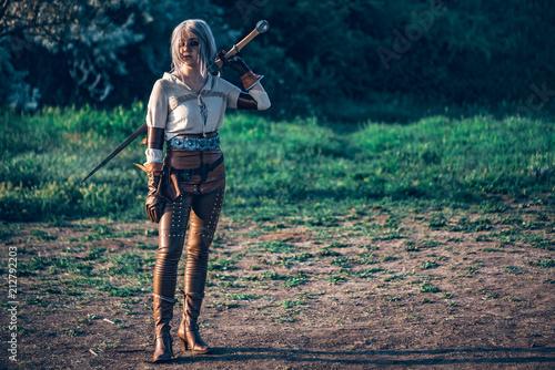 Fototapeta Fantasy cosplay beautiful Witcher girl with sword