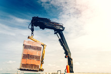 Industrial Crane Lifting And Moving Brick Pallet On Construction Site. Moving Bricks With Pallet