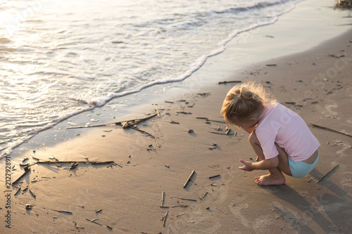 Fotografía  Little girl playing in the sand at the beach