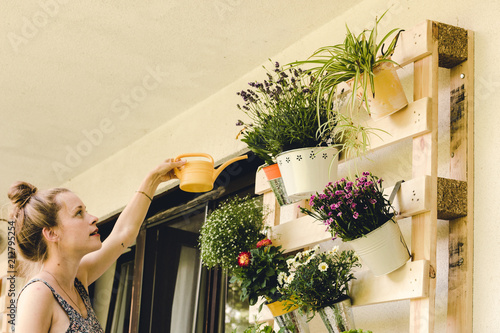 beautiful young woman watering her potted plants on the balcony