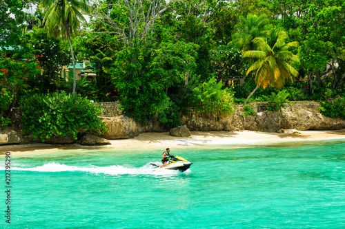 Wall Murals Green coral Jet ski rider on tropical pristine beach in Barbados