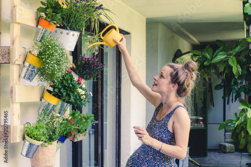 beautiful pregnant young woman watering plants on her balcony Wallpaper Mural