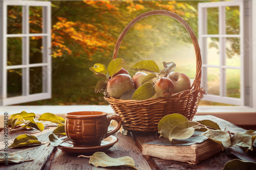 Fototapeta Apples in a basket, a plaid book, a cup on the table near a window overlooking the autumn landscape, autumn still life, the concept of coziness in a rural house during harvesting obraz
