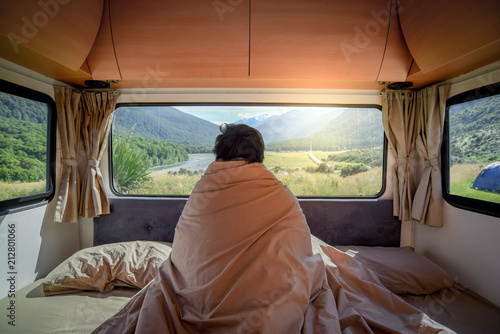 Young Asian man staying in the blanket looking at mountain scenery through the window in camper van in the morning. Road trip in summer of South Island, New Zealand.