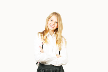 Beautiful blonde teenage girl with charming smile in schoolgirl uniform wearing pleated skirt, white shirt, backpack, hands crossed. Back to school sale concept. Background, copy space, close up.