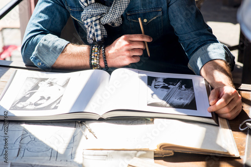 Lviv city, Ukraine, June 06, 2018 a man with a worm at the table with the drawin Tableau sur Toile