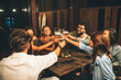 canvas print picture Group of friends drink beer on the terrace and toast during summer night