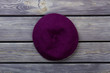 Purple beret hat on dark wood background. Top view, flat lay, wooden desk surface background.