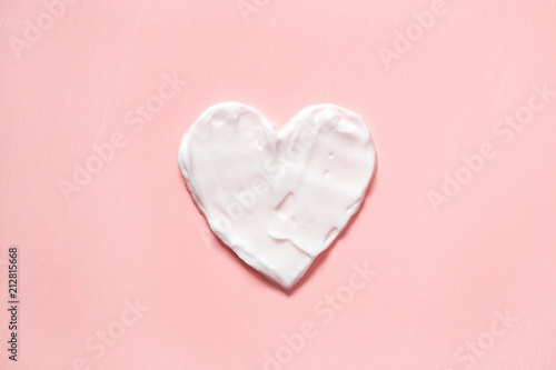 Stampa su Tela Heart shape from cream in pink background. Skin care.