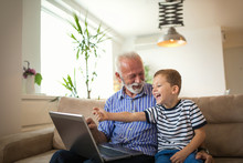 Grandfather And Grandson Using Laptop Together
