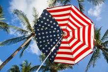 Stars And Stripes USA Flag Sun Umbrella Below Tropical Green Coconut Palms And Tropical Sky
