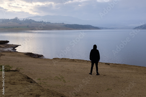 Poster  Una persona contempla el amanecer a la orilla del lago
