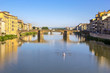Panoramic view of the Arno River and stone medieval bridge Ponte Vecchio with beautiful reflection of colorful houses and small boat, Florence, Tuscany, Italy.