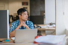Asian Designer Sitting At His Desk Deep In Thought