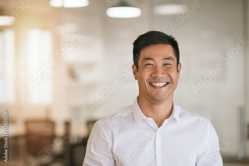 Fotografía  Smiling Asian businessman standing in a bright modern office