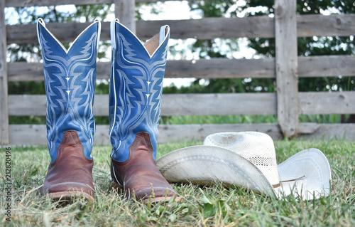 Fotografia, Obraz cowboy boots and hat with a farm gate