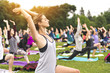 canvas print picture - big group of adults attending a yoga class outside in park