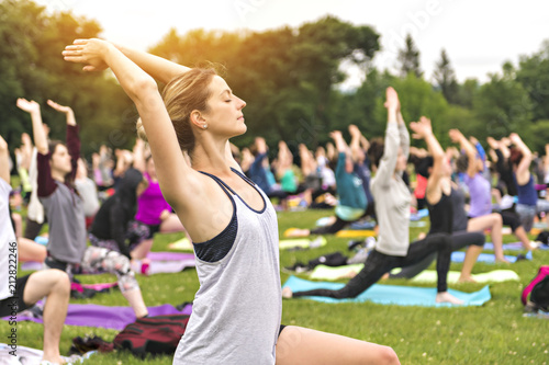 Obraz big group of adults attending a yoga class outside in park - fototapety do salonu