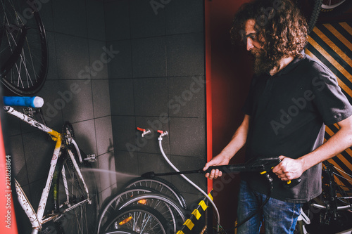 Services professional washing of a bicycle in the workshop. Close-up of hand Young Caucasian stylish man doing bicycle cleaning using automatic electric water pump. Sprays scatter from the pressure.