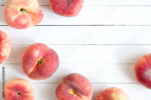Ripe juicy peaches on a wooden white background. Fruit summer background. Flat lay, top view, copy space