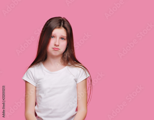 Fotografía  Brunette teen girl with sad face against pink background
