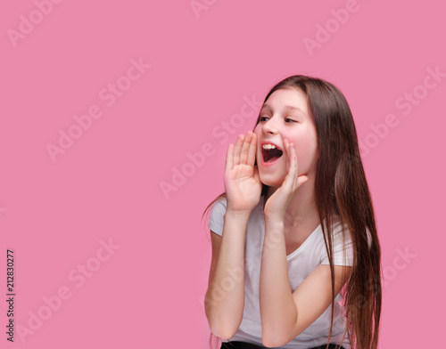 Poster  Brunette girl screaming loud to the side against pink background