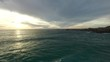 This is a drone shot of a few people surfing at sunset in Cape Town, South Africa