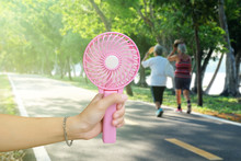 Hand Holding Pink Portable Fan...