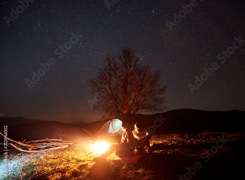 Fototapeta Camping night in mountains. Silhouettes of couple tourists sitting, man and woman lit by burning campfire under starry sky. Tent, big tree and distant hills on background. Tourism and travel concept obraz na płótnie