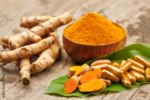 Fototapeta Turmeric powder in wooden bowls and turmeric capsules on wooden background obraz
