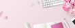 feminine banner or shop header with office / writing supplies, technical gadgets, smartphone and a bunch of pink flowers on a pink background - copyspace for your text and  branding - top view