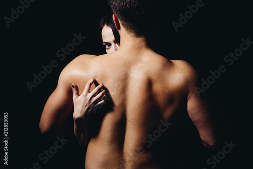 Loving his body. Woman hand touch man torso, rear view. Couple in love. He is absolutely mine. Back disease and treatment. Massage for back health. Sex games