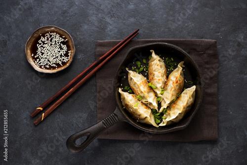 Photo  Fried dumplings Gyoza in a frying pan, soy sauce, and chopsticks on a black conc