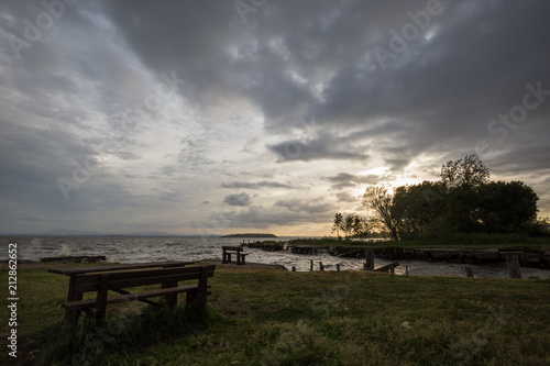 Fotografie, Obraz  A wooden sitting bench on a lake shore at sunset, beneath a moody, cloudy sky