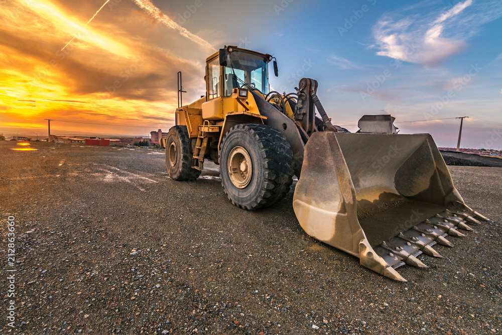 Fotografía  Excavator at the end of a working day in a construction site