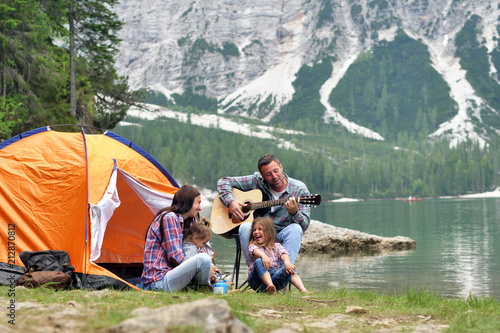 In de dag Kamperen Portrait of a happy family while they are having a good day at the lake. Concept: Love, holiday, music