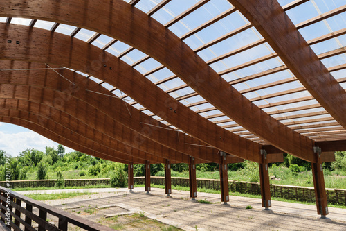 Fotografia massive wood beams roof structure with S curved shaped and covered with transpar