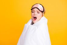 Concept Of Healthy Sleep. Sleepy Girl Yawning Wide Open Mouth Wrapped In Blanket And With Eyemask On Her Head Isolated On Yelow Background