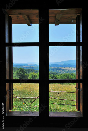 nature landscape with a view through a   wooden frame window
