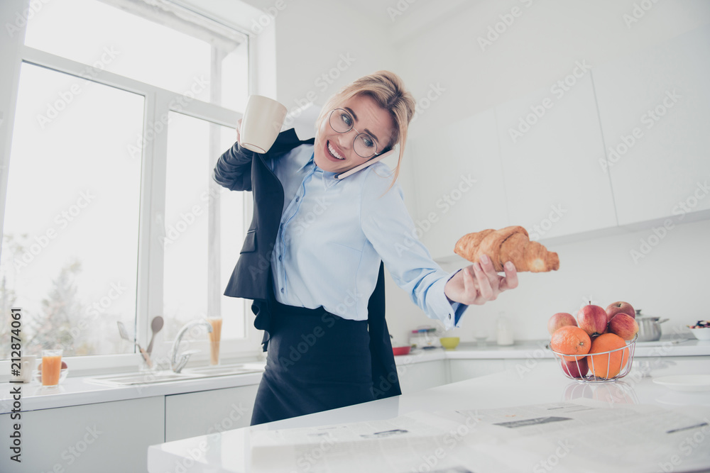 Fototapety, obrazy: Adorable busy attractive charming beautiful smiling lady office executive worker wearing spectacles in hurry early in the morning talking on the phone having a drink and croissant in kitchen