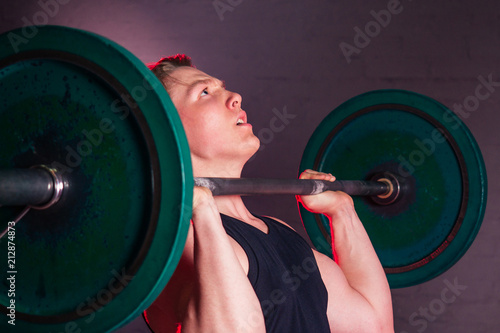 Foto op Plexiglas Fitness young handsome white man in black t-shirt is engaged with a barbell in the gym on a black brick background