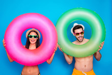 Beach Style! Travel Daydream Concept. Positive Girl And Handsome Man Look Through Colorful Rubber Rings Enjoying Rest Isolated On Blue Background