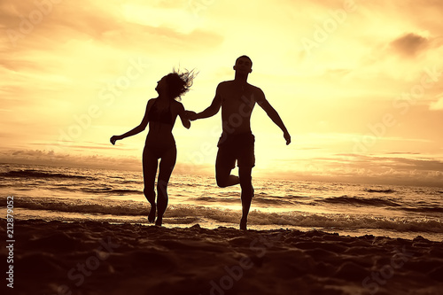Fototapeta silhouette in love sunset sea / newlyweds in honeymoon at sea, vacation luck summer sea beach, silhouette couple at sunset obraz na płótnie